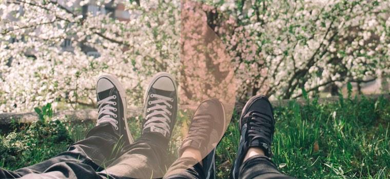 Ein Paar genießt den Frühling und liegt in der Wiese, zu sehen sind nur die Füße
