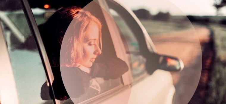 Frau schaut verträumt aus dem Auto und denkt an Mr. Right